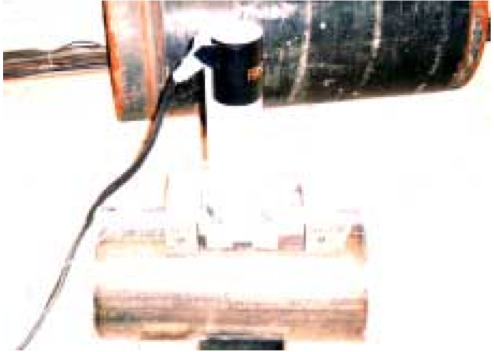 Figure 1. IIT unit magnetically attached to API 5L X60 pipe,showing umbilicals to a data processing computer.